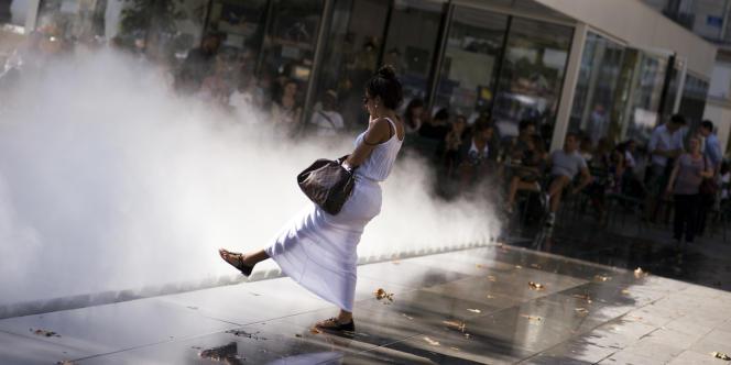 Une jeune femme se rafraîchit au brumisateur installé sur la nouvelle place de la République, à Paris.