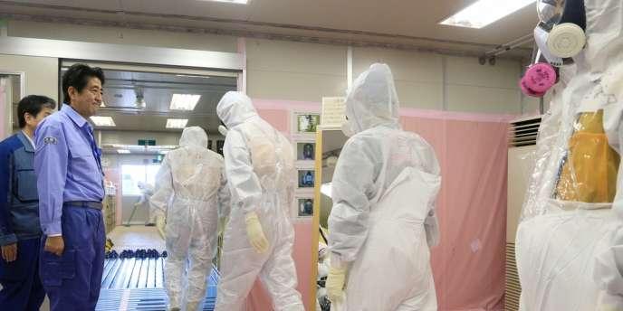Le premier ministre japonais Shinzo Abe salue des ouvriers allant décontaminer le site de Fukushima, le 19 septembre 2013.