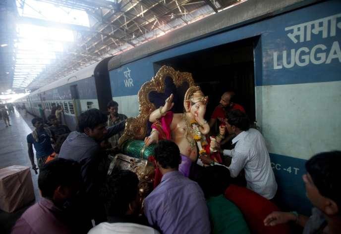 Dans une gare de Bombay, le 1er septembre, une statue du dieu Ganesh est transportée à l'intérieur d'un train pour rejoindre un lieu de culte de la mégapole indienne.