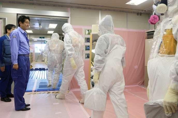 Le premier ministre japonais, Shinzo Abe, assiste le 19 septembre au départ de techniciens sur le site de Fukushima.