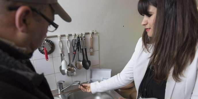 Un salarié de l'association Voisin Malin explique à un retraité comment il peut réduire sa consommation d'eau (DR).