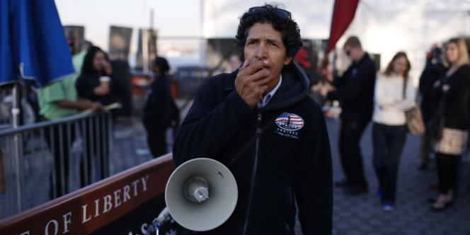 Un homme annonçant la fermeture de la statue de la Liberté aux touristes, mardi 1er octobre, à New York.