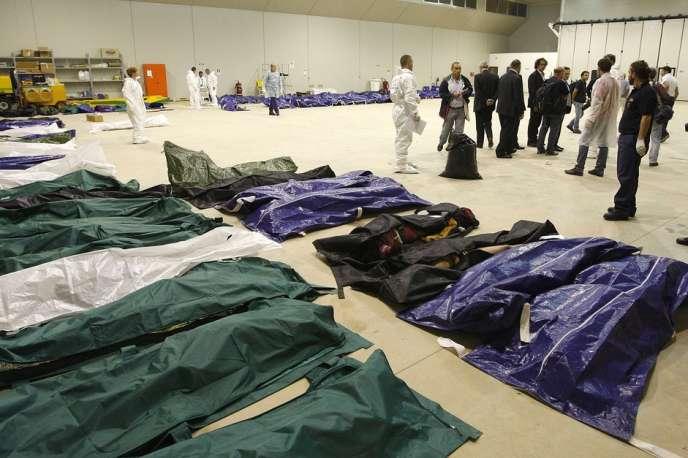 Des corps de migrants alignés dans un hangar de l'aéroport de Lampedusa, le 3 octobre 2013.
