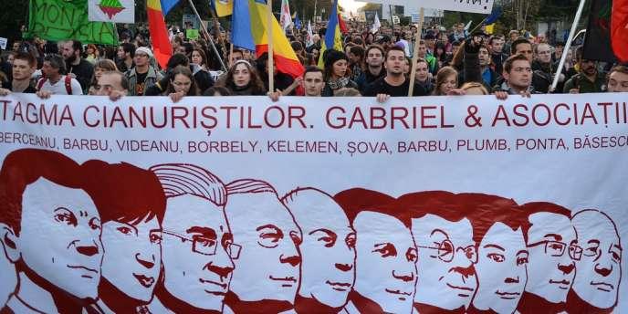 Des manifestants portent une banderole sur laquelle sont dessinés les visages des politiciens favorables au projet de mine d'or, dimanche à Bucarest.
