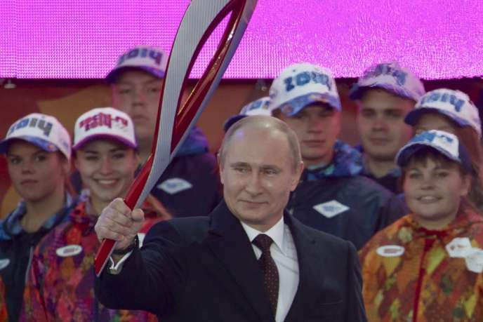 Le président Vladimir Poutine brandit la flamme olympique, dimanche 6 octobre, sur la place Rouge, à Moscou.