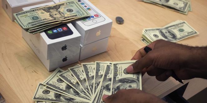 Un employé compte des billets dans le magasin Apple de Manhattan (New York), le 20 septembre 2013.