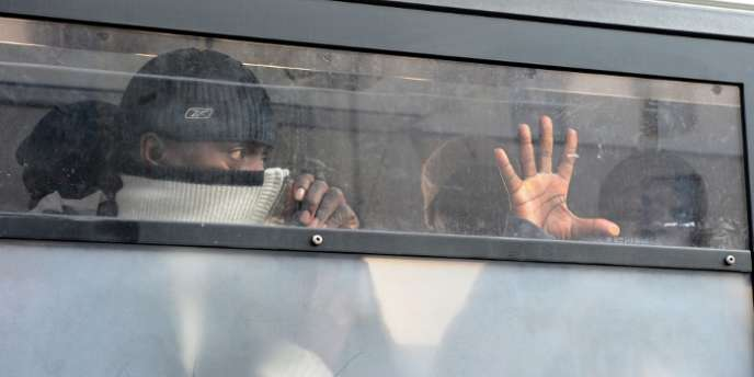 Des salariés sans papiers derrière les vitres d'un camion de police après avoir été interpelés lors de l'évacuation par les forces de police des marches de l'Opéra Bastille qu'ils occupaient pour réclamer des critères clairs de régularisation, en 2010 à Paris.