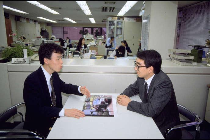 Vendeur et client chez un concessionnaire Toyota, au Japon, en 1991. La réforme du fordisme menée par ce constructeur automobile à partir des années 1960 a abouti au «lean management».
