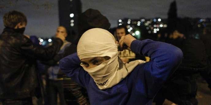 Des manifestants se préparent, dans le quartier de Biriuliovo à Moscou, le 13 octobre. Lançant des slogans racistes, les manifestants ont vandalisé plusieurs magasins où travaillent des immigrés, après l'assassinat d'un Russe de 25 ans par un homme considéré comme non slave.