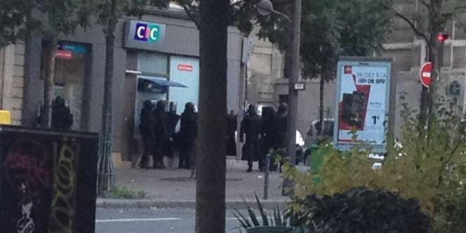 Les forces de l'ordre devant l'entrée de l'agence CIC du 77, avenue des Gobelins, où une prise d'otages est en cours.