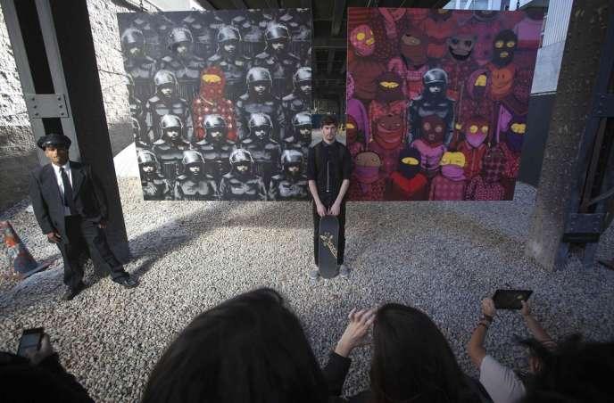 Un homme pose devant deux œuvres de Banksy affichées sous le métro de New York, le 18 octobre.