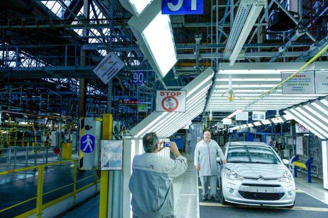 Des ouvriers posent devant la dernière Citroën C3 construite avant la fermeture de l'usine PSA Peugeot-Citroën d'Aulnay-sous-Bois le 24 octobre.