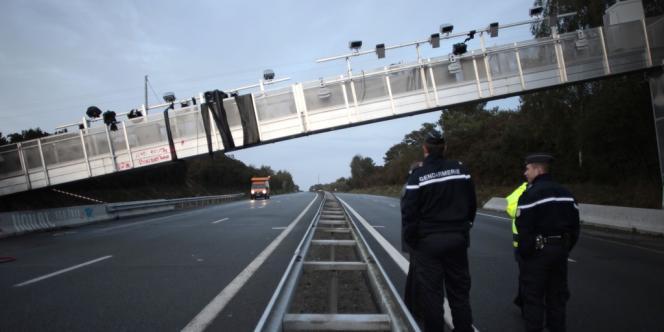 Deux policiers face à un portique écotaxe détruit à Saint-Allouestre, le 2 novembre.
