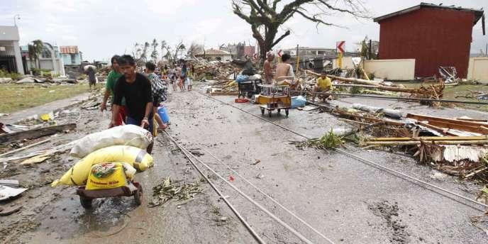 Des survivants du typhon Haiyan à Tacloban, aux Philippines, collectent des sacs de riz, le 9 novembre 2013.