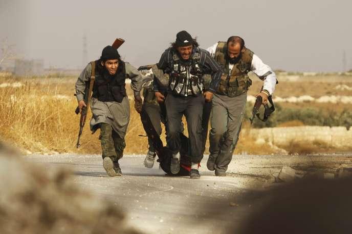 Des combattants de l'armée syrienne libre évacuent un blessé lors de combats contre l'armée syrienne autour de la base 80, près d'Alep, dans le nord de la Syrie, le 8 novembre 2013.