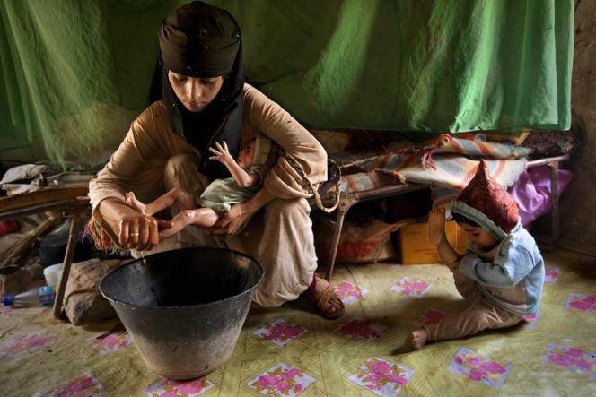 Un toute jeune fille yéménite baigne son deuxième enfant.
