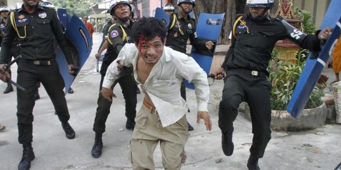 Un travailleur du textile cambodgien blessé fuit la police anti-émeute dans l'enceinte d'une pagode bouddhiste à Phnom Penh, au Cambodge, le mardi 12 novembre 2013.