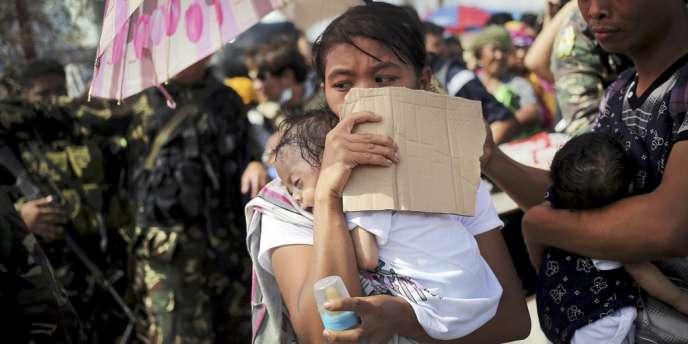 A Tacloban, au centre des Philippines, une femme et son enfant attendent d'être évacués après le passage du typhon Haiyan.