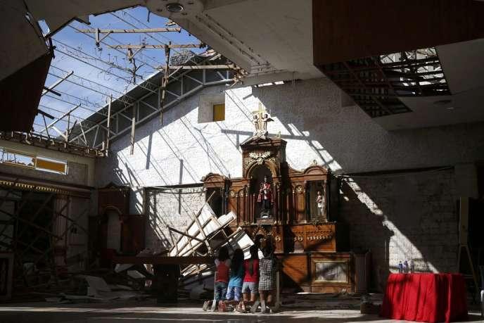 Des victimes du typhon prient devant l'autel d'une église détruite, à Cebu, le 17 novembre.
