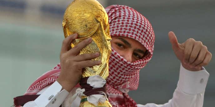 Un jeune Qatari brandit une copie de la Coupe du monde après l'annonce par la FIFA, en 2010, que cet Etat du Golfe accueillerait le Mondial de football 2022.