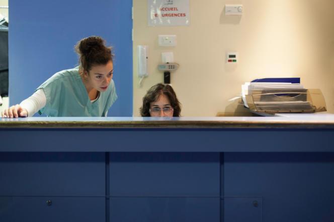 Une infirmière et la secrétaire de l'accueil des urgences font le tri des priorités parmi les patients.