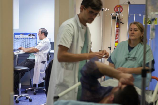 Une aide-soignante et un infirmier s'occupent de préparer un patient avant une intervention en urgence.