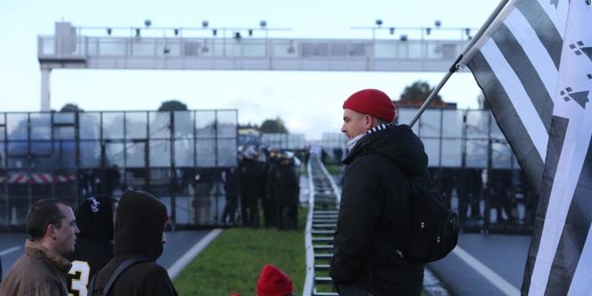 Des membres des «bonnets rouges» au pied du portique écotaxe, à Montauban-de-Bretagne, le9novembre2013.