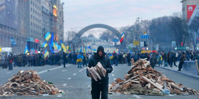Un homme récolte du bois afin d'alimenter les braseros, qui permettent aux manifestants de se réchauffer, à Kiev, en Ukraine, le 4 décembre.