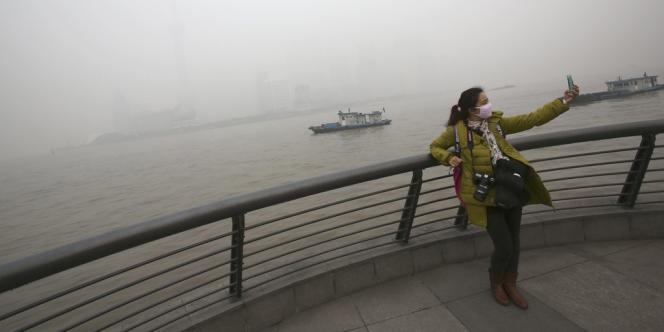 Une touriste se prenant en photo dans le brouillard de pollution qui paralysait la ville de Shanghaï, vendredi 6 décembre.