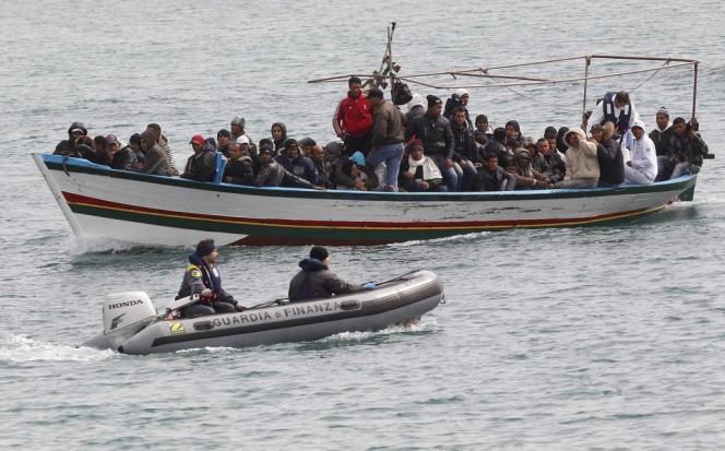 Une embarcation de migrants venue d'Afrique du Nord, escortée par un Zodiac italien de la Guardia di finanza, en mars 2011.