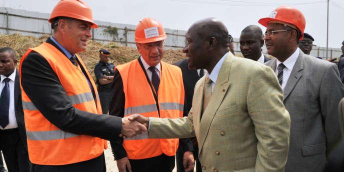 Le premier ministre ivoirien, Daniel Kablan Duncan (au centre) en janvier 2013 lors d'une visite sur un chantier du pont Henri Konan Bedie à Abidjan, conduit par le groupe français Bouygues.
