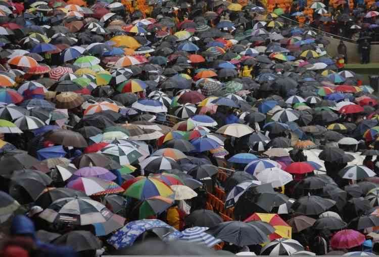 A sea of umbrellas in the arena as rain lashes down during the memorial service for former South African president Nelson Mandela at the FNB Stadium in Soweto, near Johannesburg, South Africa, Tuesday Dec. 10, 2013. (AP Photo/Tsvangirayi Mukwazhi)