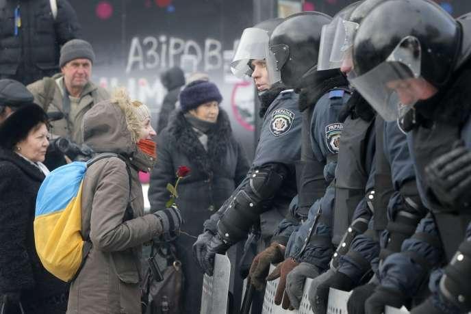 Une manifestante ukrainienne pro européenne face aux policiers antiémeute dans le centre de Kiev mardi 10 décembre.