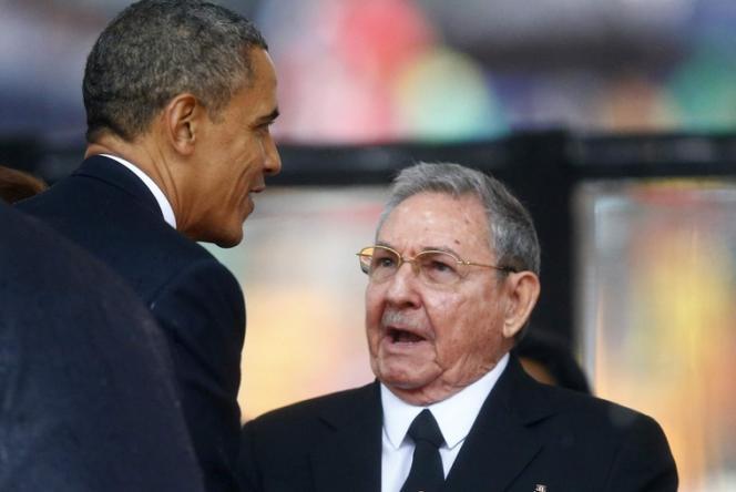 Poignée de main historique entre Barack Obama et le président cubain, Raul Castro, sous les yeux de Dilma Rousseff, la présidente du Brésil, lors de l'hommage à Mandela, le10décembre2013.