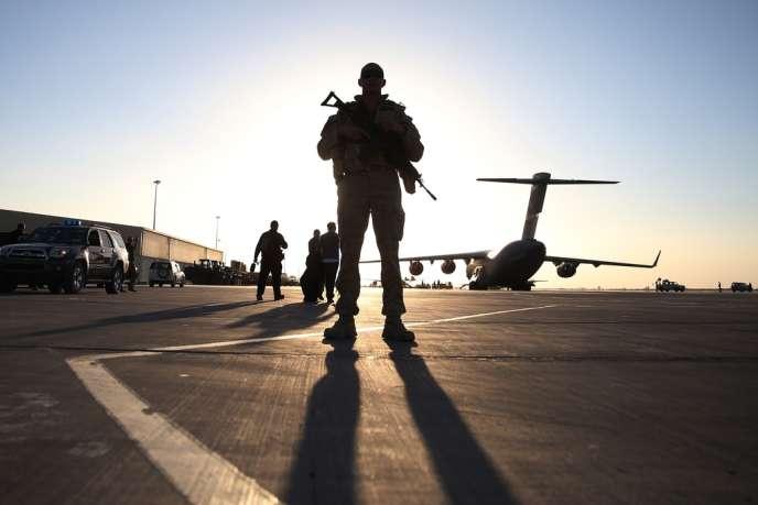 En Afghanistan, le 3 décembre 2014 verra le départ du dernier soldat de l'OTAN – ses troupes s'élèvent à environ 45 000 hommes (ici, un soldat américain derrière un C-17 sur le tarmac de Kandahar, le 8 décembre 2013).