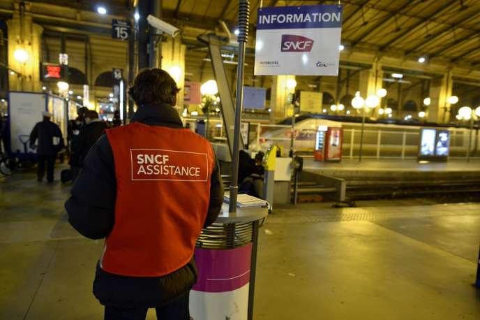 Un employé chargé de guider les passagers à la gare du Nord, à Paris, le 11 décembre.
