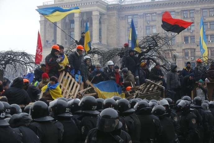 Les manifestants pro-européens font face aux policiers antiémeute place de l'Indépendance, aux premières heures du jour, mercredi.