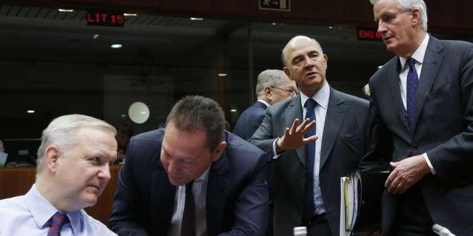 Le commissaire européen aux affaires économiques et monétaires, Olli Rehn, le ministre des finances grec Yannis Stournaras, son homologue français Pierre Moscovici et le commissaire européen au marché intérieur, Michel Barnier à Bruxelles, le 10 décembre.