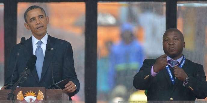 Le président américain Barack Obama prononce un discours à côté d'un interprète en langue des signes au cours de la cérémonie commémorative pour Nelson Mandela, à Johannesburg le 10 décembre.