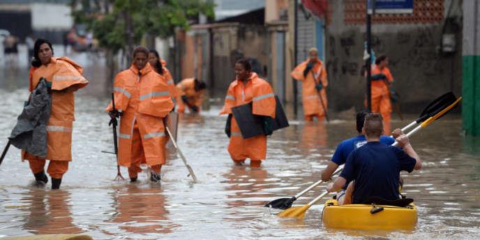 Des travailleurs municipaux dans une rue inondée d'une banlieue de Rio de Janeiro, le 11 décembre.