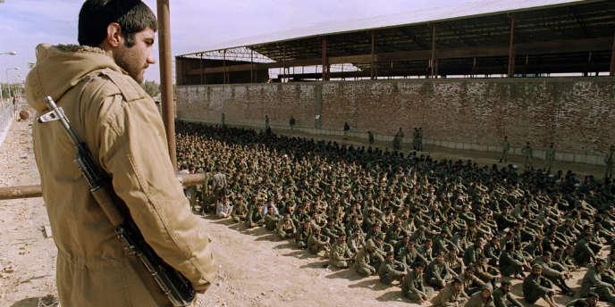 En janvier 1987, près d'Ahvaz (Iran), un soldat iranien surveille des prisonniers irakiens.