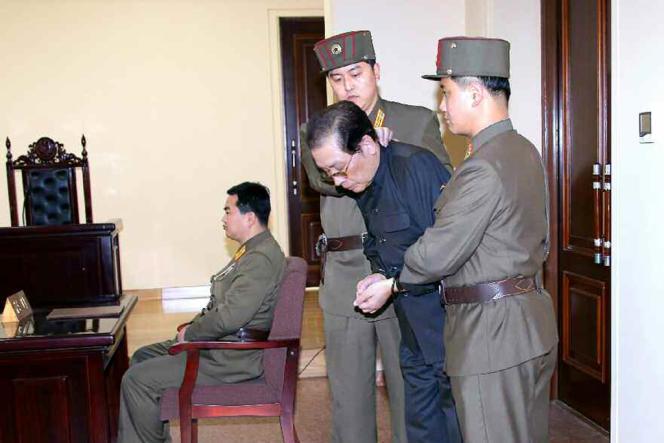 Jang Song-taek escorté par deux officiers dans une cour de justice, peu de temps avant son exécution, le 12 décembre.