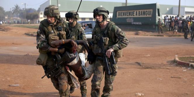 Des soldats français évacuent un homme grièvement blessé lors d'un rassemblement devant l'aéroport de Bangui, lundi 23 décembre.