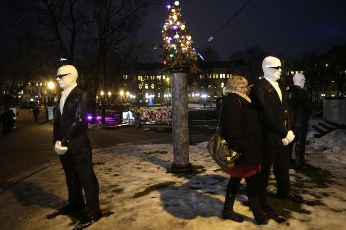 Une femme prend la pose, jeudi 12 décembre, près de l'œuvre de l'artiste letton Einars Timma, « Le Sapin de Noël des VIP », installée dans le centre de Riga.