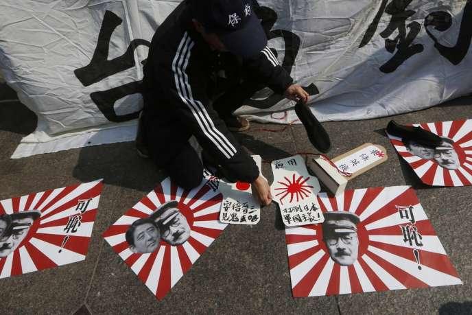 Hong-Kong, le 27 décembre. Manifestation devant le consulat du Japon contre le premier ministre Shinzo Abe qui s'est rendu au sanctuaire de Yasukuni. Au sol des affichettes le représentent avec le général Hideki Tojo de l'armée impériale du Japon. Ce dernier, condamné pour crimes de guerre par le tribunal de Tokyo en 1948, fut pendu le 23 décembre 1948.