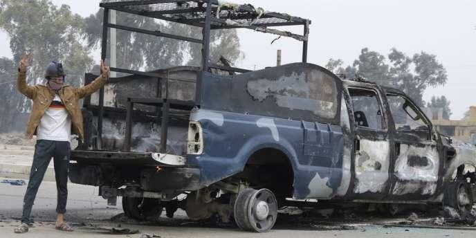 Un protestataire près d'un véhicule de police incendié, lundi 30 décembre, après le démantèlement du campement sunnite de Ramadi.