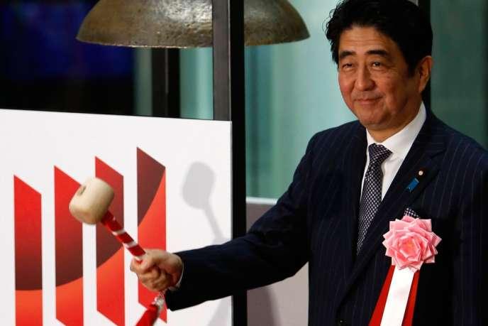 Le  premier ministre japonais, Shinzo Abe, sonne la clôture de la dernière séance de la Bourse de Tokyo, le 30 décembre 2013.