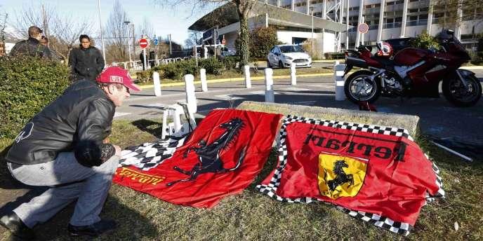 Un fan de l'écurie Ferrari et de Michael Schumacher dépose des drapeaux devant le CHU de Grenoble, le 30 décembre.