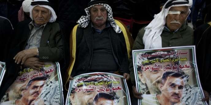 Des Palestiniens portent le portrait d'un des prisonniers libéré, Na'em Al-Shawamreh.