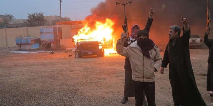 Des opposants irakiens brûlent une voiture militaire lors des affrontements qui ont éclaté lundi, à la suite du démantèlement d'un camp sunnite par les forces de sécurité.